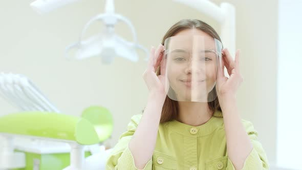 Thumbnail for Happy Dentist Dressing Up Protective Mask in Dental Clinic. Young Doctor