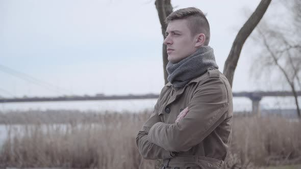 Sad Caucasian Man Standing on Riverbank and Thinking. Portrait of Young Depressed Lonely Guy
