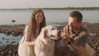 Couple Petting Dog on Seashore