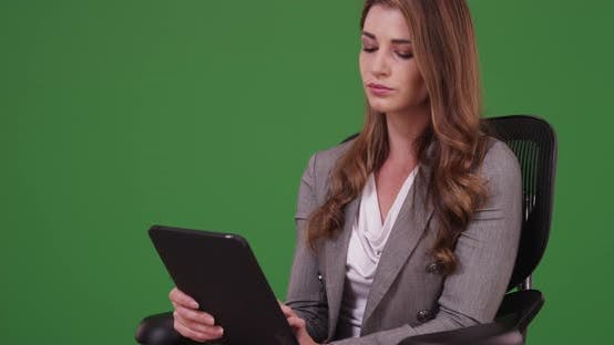 Thumbnail for Businesswoman in her 20s using tablet while sitting on her chair on green screen