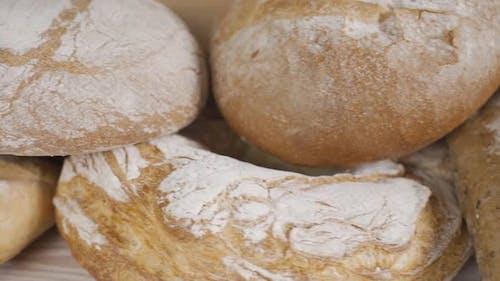 Frisches Vollkornbrot auf dem Holztisch. Verschiedene Bäckerei Brot. Dolly Shot. Zeitlupe. Schließen