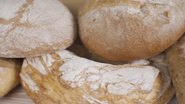 Thumbnail for Frisches Vollkornbrot auf dem Holztisch. Verschiedene Bäckerei Brot. Dolly Shot. Zeitlupe. Schließen