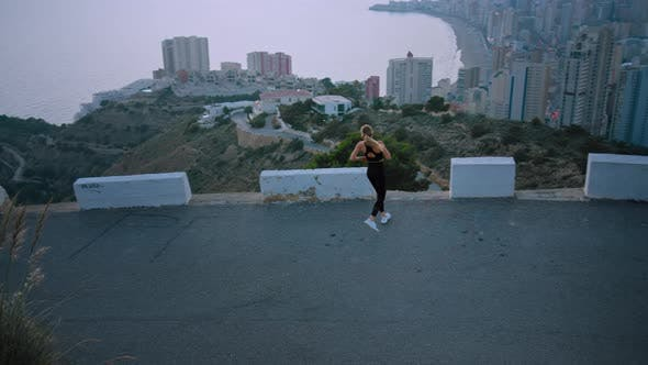 Strong Fit Female Athlete Run Over City at Sunrise
