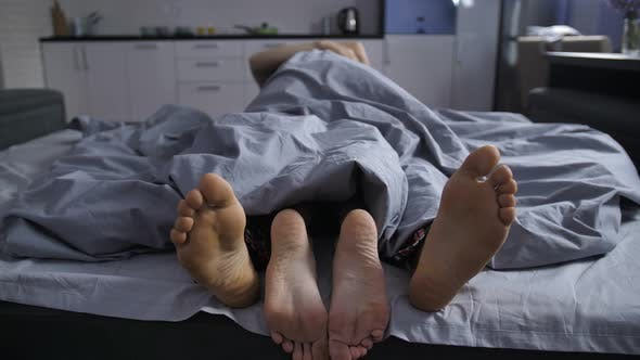 Thumbnail for Feet of Affectionate Couple Cuddling in Bed