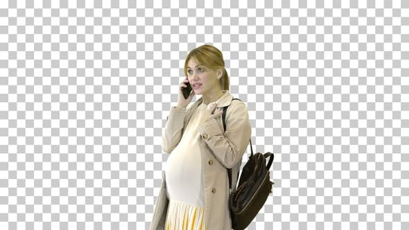 Pregnant woman in a cloak with backpack talking on the - product preview 0