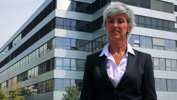 Thumbnail for Business Middle Age Woman Agrees and Shakes with Head - Company Building in the Background