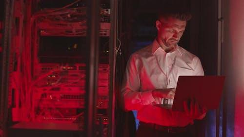 Businessman Using Laptop in Datacenter Room