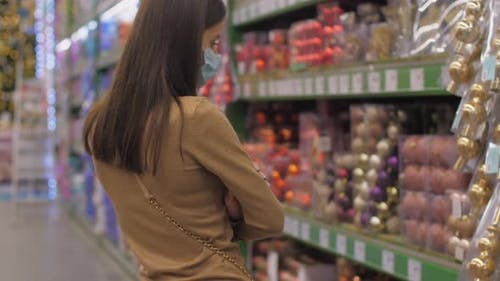 Professional Shopaholic in Mask Looks at Different Baubles