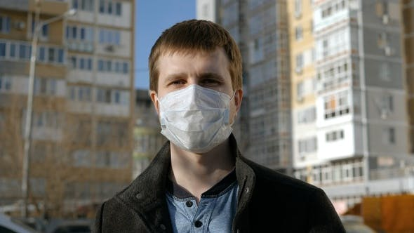 Thumbnail for Man in A Surgical Mask Standing Outdoors and Looking to Camera