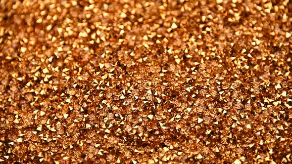 Thumbnail for Abstract background of golden rhinestones spinning