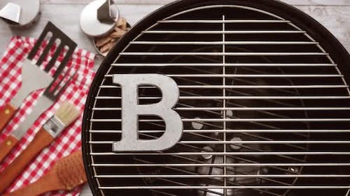 Metal BBQ sign with BBQ cooking tools on a wood background