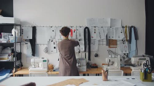 Tailor Young Lady Touching Drawings on Wall Planning New Clothes Collection