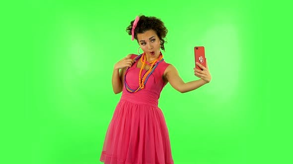 Thumbnail for Young Woman Makes Selfie on Mobile Phone Then Looking Photos on Green Screen