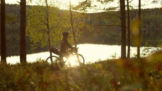 Woman Bikepacking in Autumn Nature on Bicycle