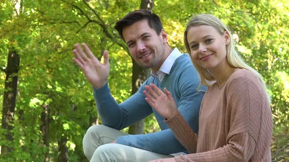 Thumbnail for A Man and a Woman Sit in a Park on a Sunny Day and Wave at the Camera with a Smile