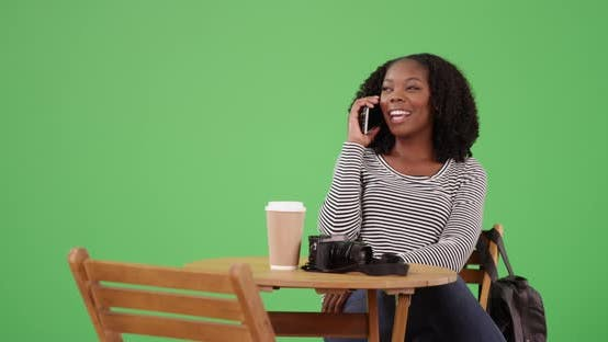 Thumbnail for Cute black woman sitting at table talking to friend on cellphone on green screen