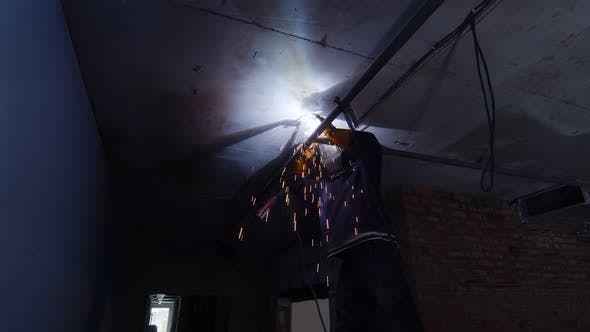 Thumbnail for A Welder on a Construction Site Welds an Iron Pipe Under the Ceiling of the Room. The Welder Works