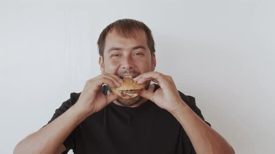 Thumbnail for Happy Man Eating Tasty Fast Food Burger