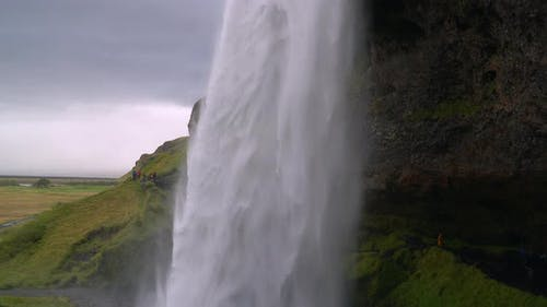 Water Flows in a Powerful Stream Down the Waterfall