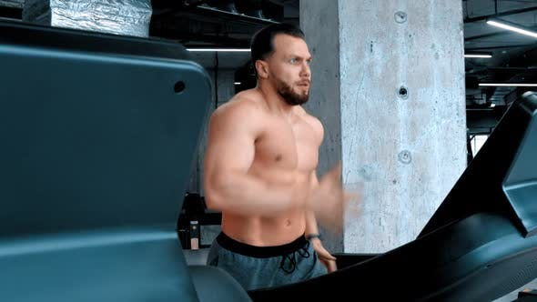 A Bearded Attractive Man Bodybuilder Running on the Treadmill with an Effort