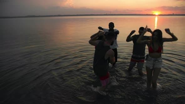 Thumbnail for Unbeschwerte Menschen tanzen bei Sonnenuntergang
