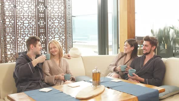 Thumbnail for Relaxed Diverse Friends in Bathrobes Relaxing at Lounge Zone of Bathhouse
