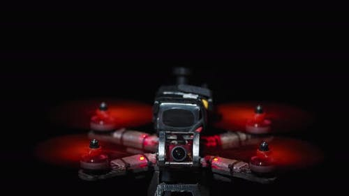 FPV Drone with Red Propellers Spinning Black Background