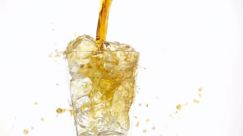 Pouring Cola into a Glass with the Ice Cubes