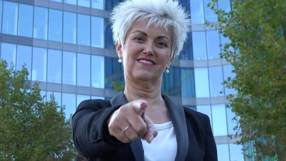 Thumbnail for A Middle-aged Businesswoman Points at the Camera with a Smile in an Urban Area - Office Building