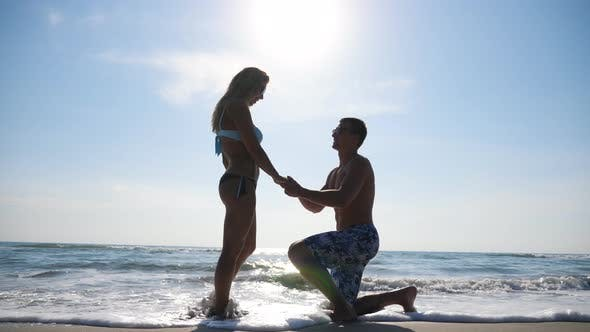 Cover Image for Young Man Stand on Knee and Marriage Proposal To His Girlfriend Summer Vacation. Happy Pair Hugging