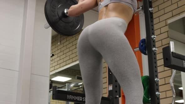 Fitte Frau hocken mit Langhantel im Fitnessstudio