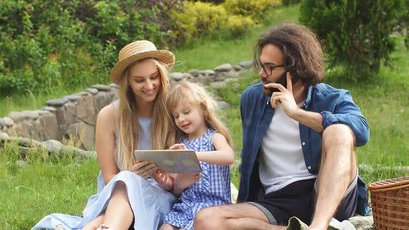 Thumbnail for Beautiful Young Family Using Digital Tablet During Picnic at Countryside,