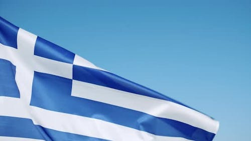 Close Up Crop of Greek Flag Flying on the Calm Wind Flutters with Bright Blue Sky in Background