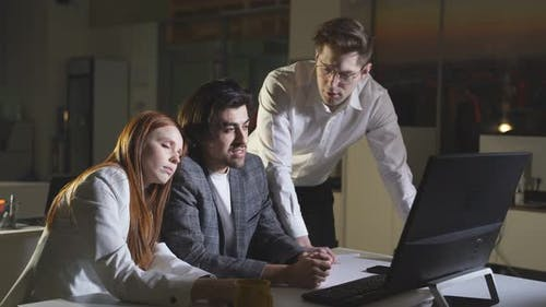 A Team of Young People Works Hard Late at the Office at the Computer Works Overtime