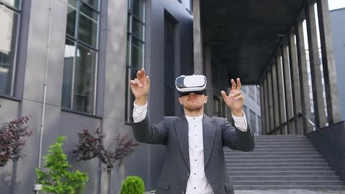 Young Male Office Worker in Virtual Reality Headset Working on Imaginary Screen