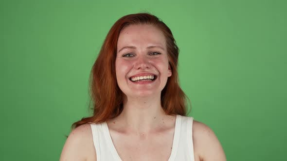 Thumbnail for Happy Woman Smiling, Celebrating Success on Green Background
