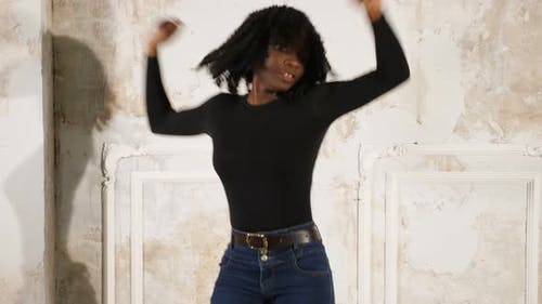 Black Woman in Jeans and Pullover Dances in High Heels