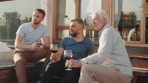 Men Talking and Toasting with Wine on Terrace during family weekend