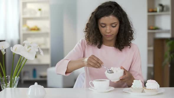 Thumbnail for Young woman adding too much sugar in tea cup, unhealthy lifestyle, diabetes