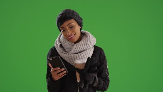 Thumbnail for African American woman in scarf and coat messaging on cell phone on green screen