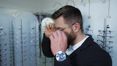 Man choosing glasses at optical store. Young man in optical store trying eyeglasses
