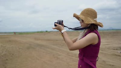 traveller woman taking a photo with camera in countryside