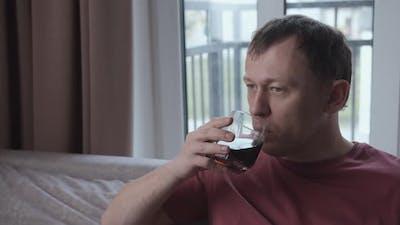 Sad Man Drinking Alcohol While Sitting on Sofa Window Background