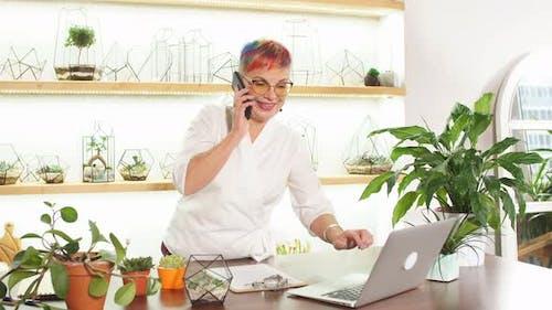 Top View on Senior Woman Florist Talking on Phone Standing Around Plants