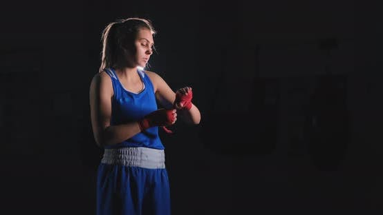 Cover Image for Medium Shot of an Athletic Female Boxer Pulls Red Bandages on the Hands of a Female Fighter