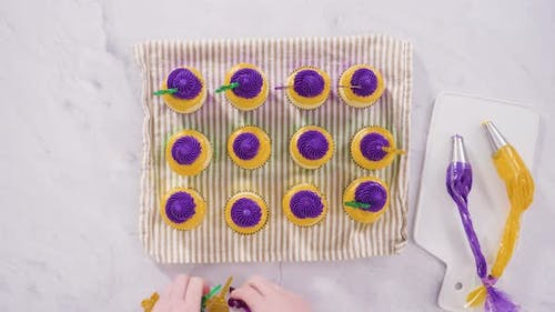 Flat lay. Step by step. Frosting vanilla cupcakes with Italian buttercream icing for Mardi Gras cele
