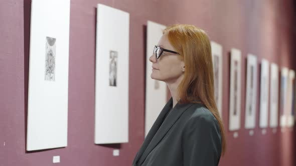 Thumbnail for Thoughtful Redhead Woman Looking at Artworks in Gallery