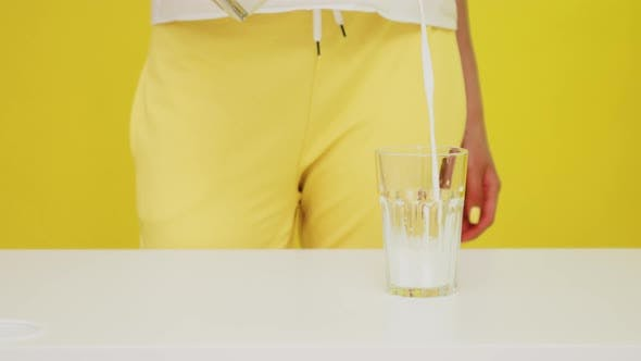 Milk Is Poured Into Glass By Woman