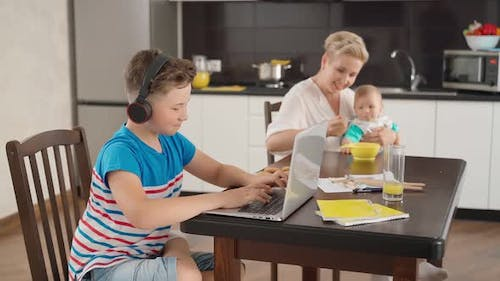 Boy Playing on Laptop While Woman Feeding Baby