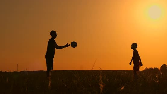 Thumbnail for Father and Son Playing Football in the Park at Sunset, Silhouettes Against the Backdrop of a Bright